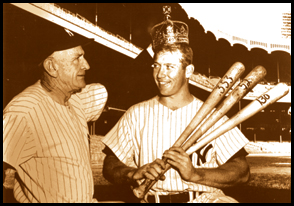 Mickey Mantle holds three baseball bats to indicate his Triple Crown winning numbers in 1956: .353 average, 52 home runs and 130 rbi. Casey Stengel crowns Mickey with the Sultan of Swat crown for best slugging average in 1956, too.
