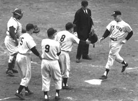 Mickey Mantle is greeted by temmates after belting a left-handed grand slam home run into the left-centerfield upper deck at Ebbets Field against the Brooklyn Dodgers in Game 5 of the 1953 World Series